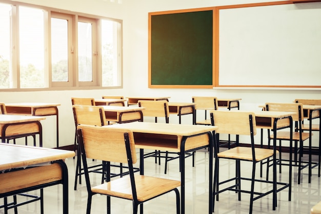 Empty school classroom with desks chair wood, green board and ...
