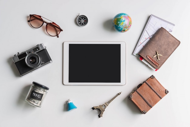 Empty screen tablet with travel accessories and items on white background Premium Photo