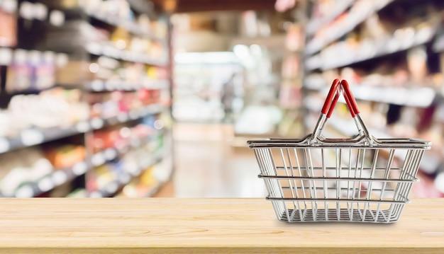 食料品店のスーパーマーケットの木製のテーブルに空のショッピングバスケットは、背景をぼかし Premium写真