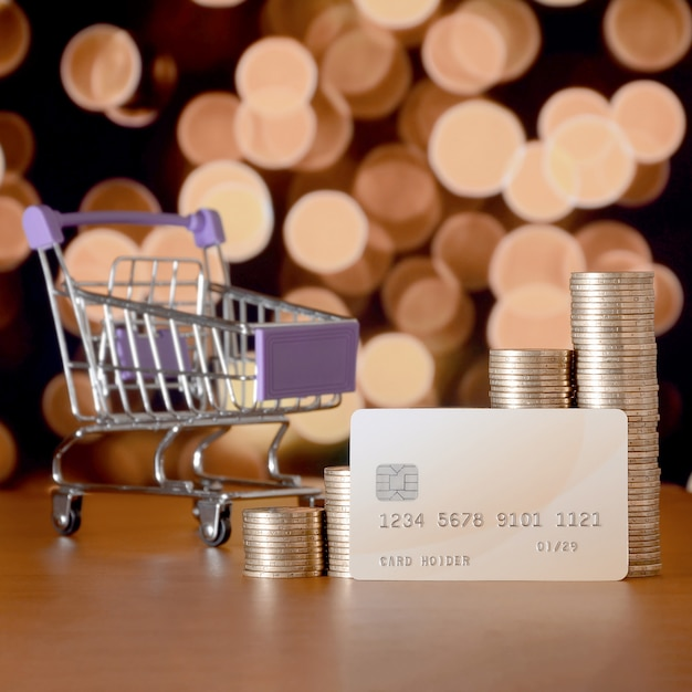 Empty shopping cart and money stacks in growth graph at the beige credit card Premium Photo