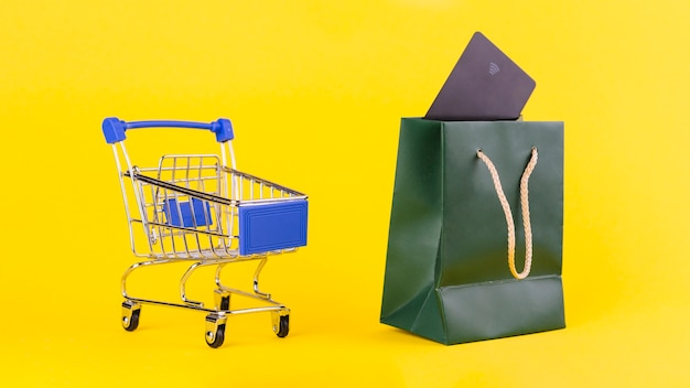 An empty shopping cart near the shopping bag with travel card against yellow background Free Photo