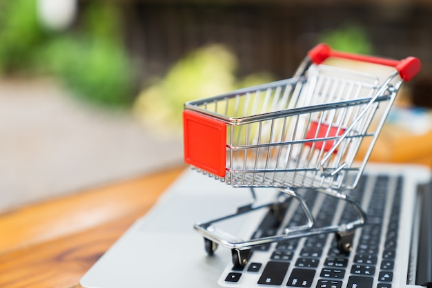 05776ce4f53 Empty shopping cart on table with laptop keyboard and copy space for online  shopping concept Premium Photo