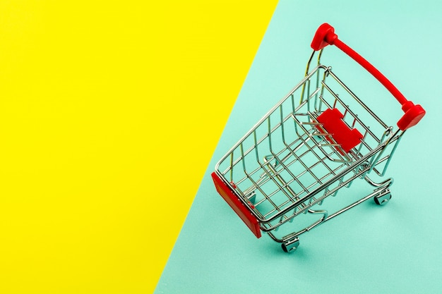 Empty shopping cart on yellow and blue background Premium Photo