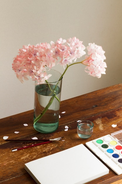 Empty sketch book with watercolor and flowers in vase at art workspace Free Photo