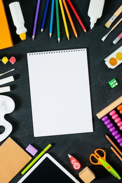 ブラックボードの背景に学用品の空のスケッチブック。学校のコンセプトに戻る。フレーム、flatlay、コピーテキストのスペース。モックアップ Premium写真