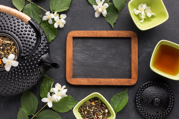 Empty slate with dried herbs and white jasmine flower on black background Free Photo