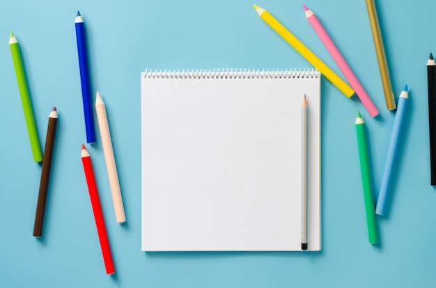 Empty square notebook and set of colorful pencils on blue background. blank paper. Premium Photo