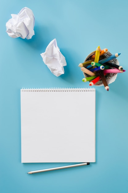 Empty square notebook, set of colorful pencils and crumpled up papers. blank paper. Premium Photo