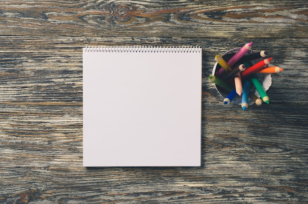 Empty square notebook and set of colorful pencils on the wooden table. blank paper. Premium Photo