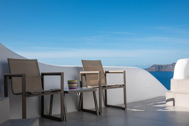 Empty table and chair with blue sky in santorini island, greece Premium Photo