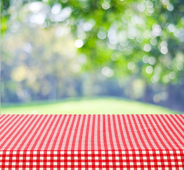 Empty Table With Red And White Tablecloth Over Blurred Park Nature Outdoor Background