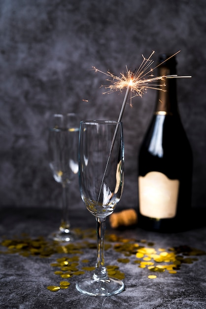 Empty transparent wine glass with christmas sparkler on cement concrete background Free Photo