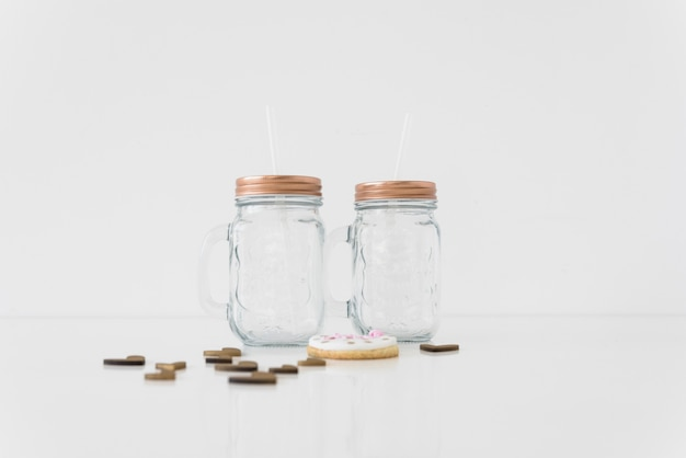An empty two transparent mason jars with hearts and cookie on white background Free Photo