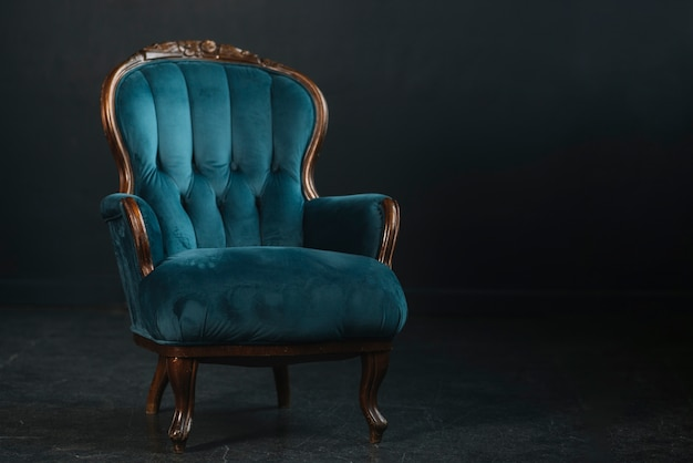 An empty vintage royal blue armchair against black background Free Photo