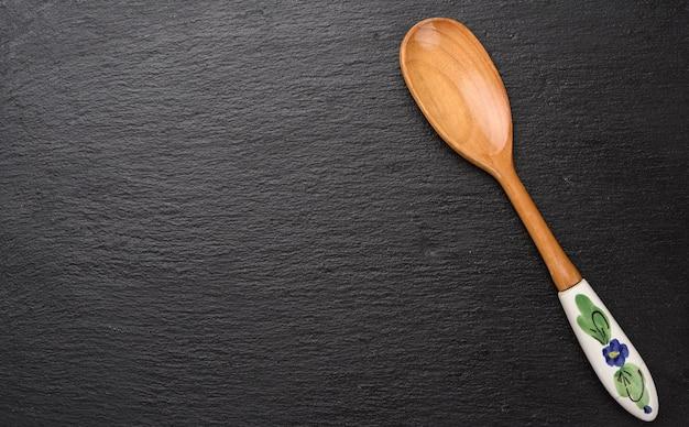 Пустая старинная деревянная ложка с керамической ручкой на черном фоне, вид сверху Premium Фотографии