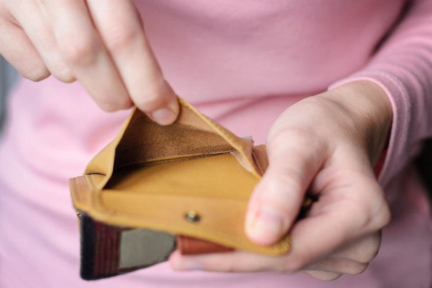 Empty wallet in the hands of a young woman in a pink sweater. Premium Photo