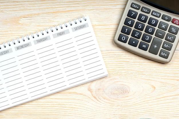 Пустой недели планировщик с калькулятором на офисном столе, концепция рабочего места Premium Фотографии
