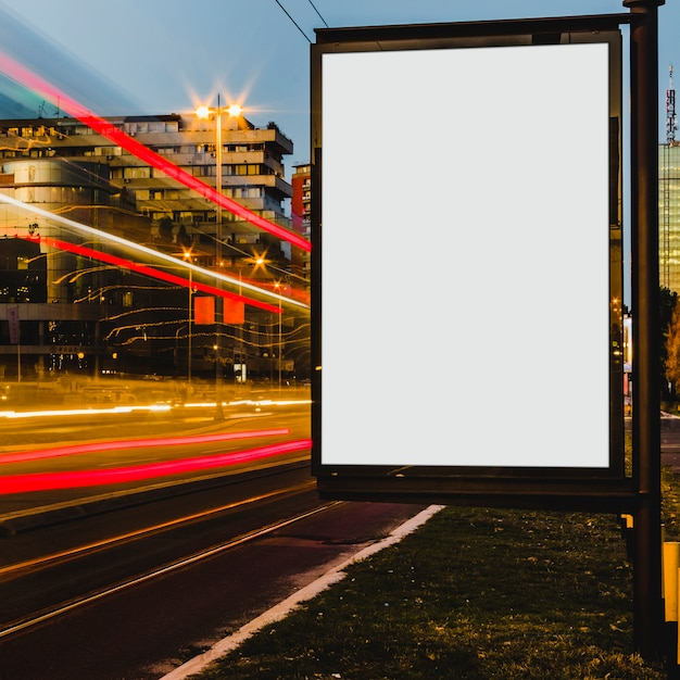 An empty white billboard with light trails in the city at night Free Photo