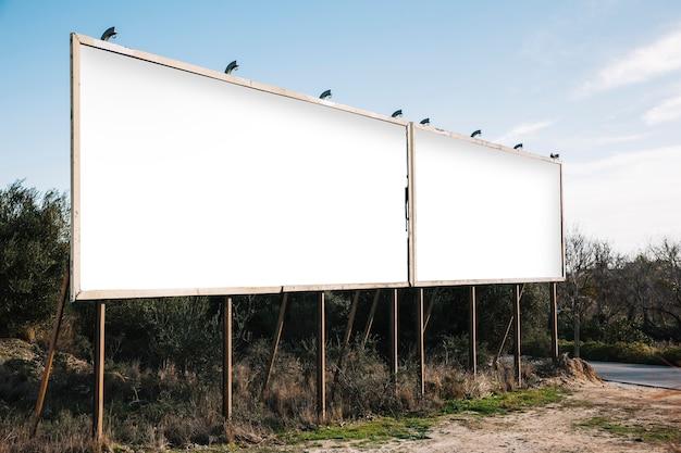 Empty white billboards on suburban roadside Free Photo