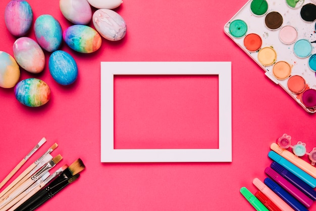 An empty white border frame with easter eggs; paint brushes; felt tip pens and water color paint box on pink background Free Photo