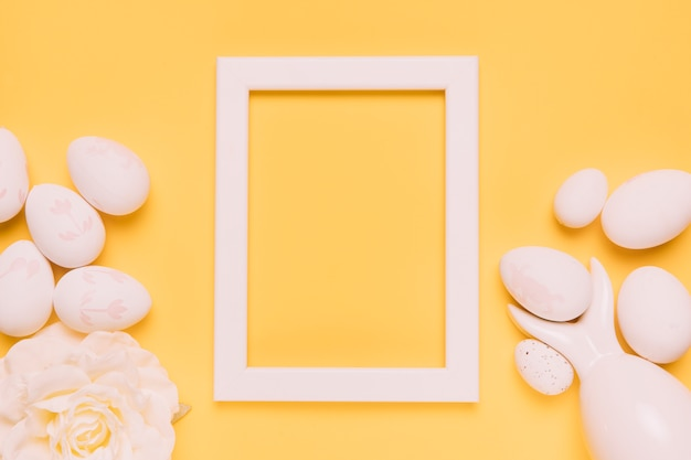 An empty white border frame with easter eggs and rose on yellow background Free Photo