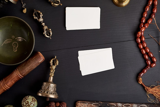 Empty white business cards in the midst of asian religious objects Premium Photo