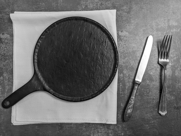 Empty white ceramic plate with knife and fork on gray stone concrete table background. copy space. menu recipe concept Premium Photo