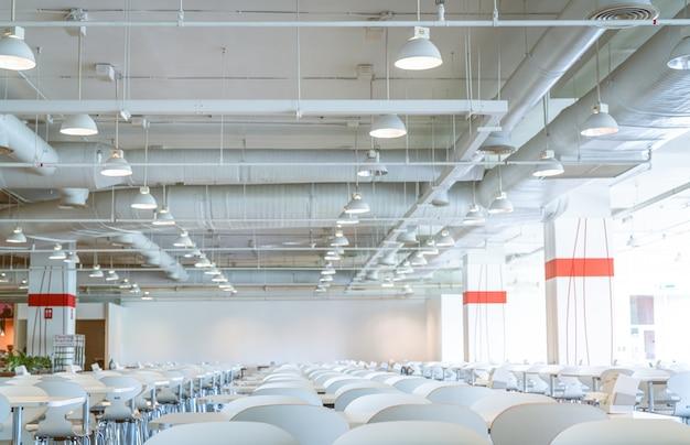 Kursi dan meja putih kosong di kafetaria pusat pemerintahan.  saluran udara, pipa AC, dan sistem penyiram api.  ventilasi sistem.  bangunan interior.  lampu lampu langit-langit.  Foto Premium