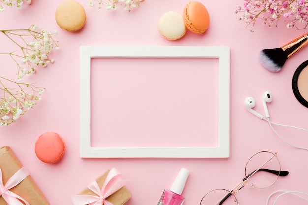 Empty white frame surrounded by make-up accessories Free Photo