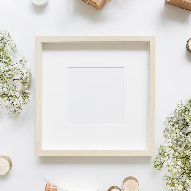 An empty white frame surrounded with flowers and gift boxes Free Photo