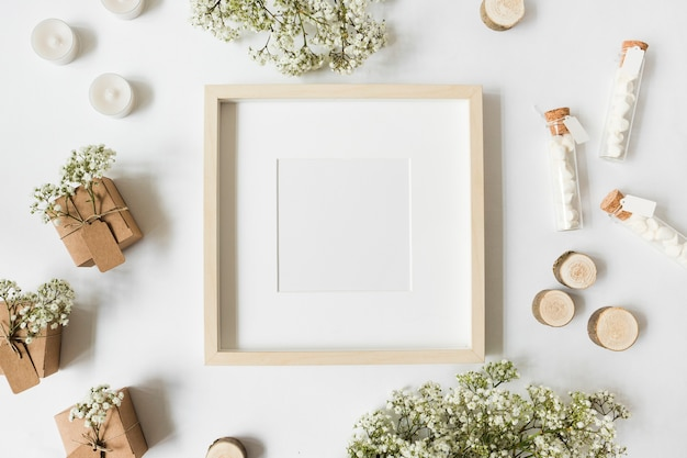 An empty white frame surrounded with gift boxes; candles; tree stump; marshmallow test tubes and baby's-breath flowers on white backdrop Free Photo