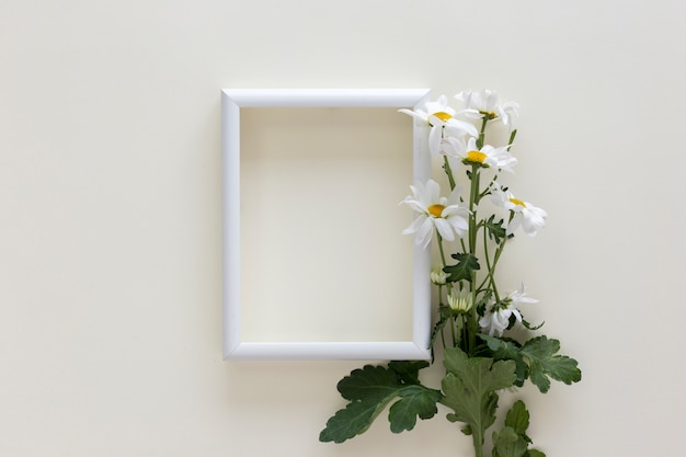 Empty white frame with flowers over isolated on white background Free Photo