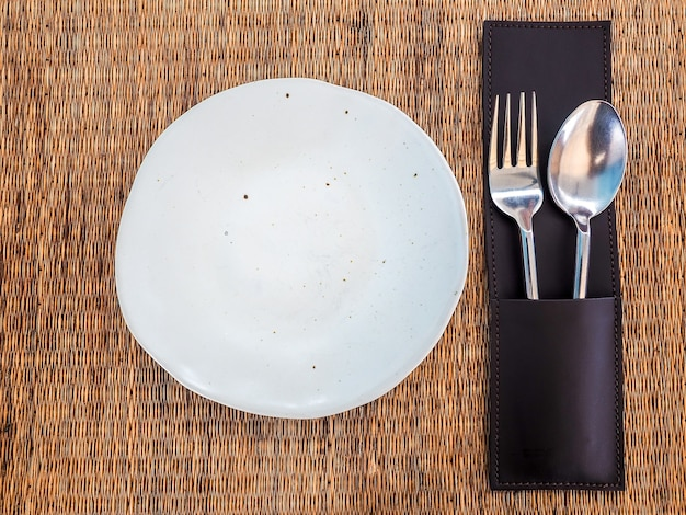 Empty white freeform shaped porcelain dish with stainless spoon and fork in leather case on mat Premium Photo