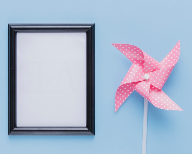 Empty white photo frame with pink pinwheel over blue backdrop Premium Photo