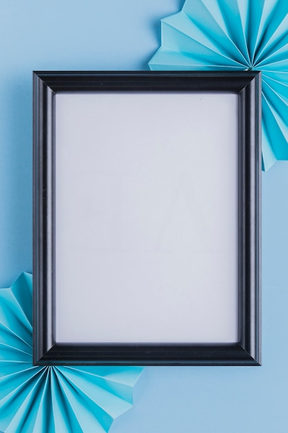 Empty white picture frame and origami fan over blue backdrop Free Photo