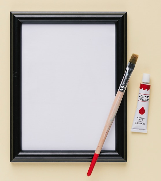 Empty white picture frame with paint tube and paintbrush Free Photo
