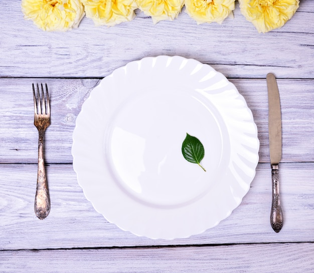 Empty white plate and metal fork and knife Premium Photo