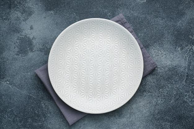 Empty white plate on a napkin dark stone table. copy space. Premium Photo