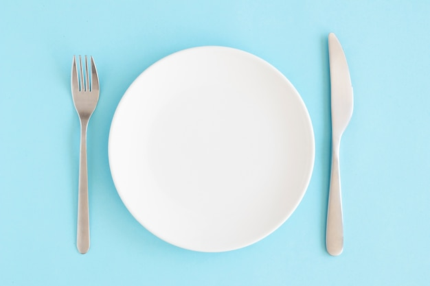 Пустая белая тарелка с вилкой и масляным ножом на синем фоне Premium Фотографии