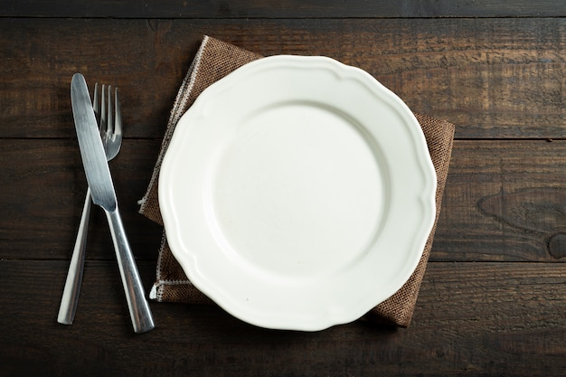 Empty white plate on wood table. Free Photo