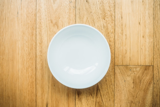 Empty white plate on wooden background Free Photo
