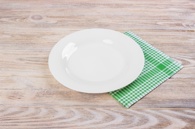 Empty white plate on wooden table Premium Photo