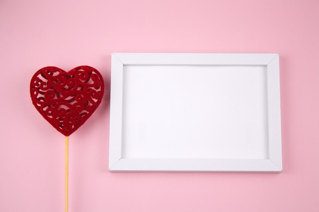 Empty white wooden frame and red heart on a pastel pink background Premium Photo