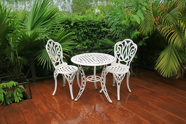 Empty white wrought iron garden tea table and chairs in the patio after rain Premium Photo