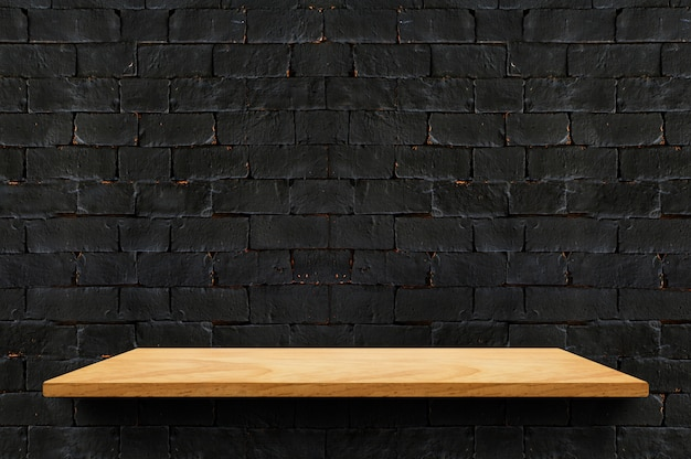 Empty wood board shelf at black brick wall background for display product Premium Photo