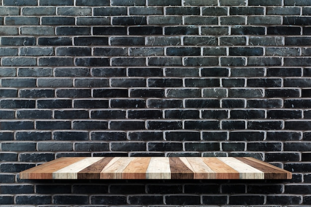 Empty Wood Board Shelf At Black Brick Wall Background Photo