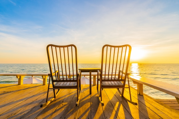 Empty wood chair and table at outdoor patio with beautiful tropical beach and sea Free Photo