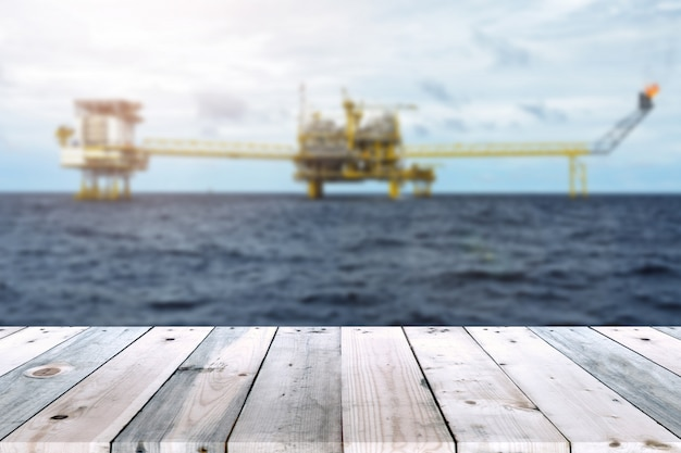 Empty wood plank table with oil and gas platform or construction platform offshore rig blur background. Premium Photo