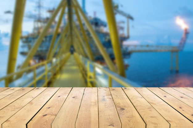 Empty wood plank table with oil and gas platform or construction platform offshore rig blur background Premium Photo