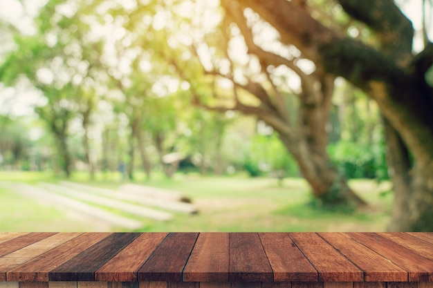 Empty wood table and blurred greenery of garden trees in sunlight. display montage for product. Premium Photo
